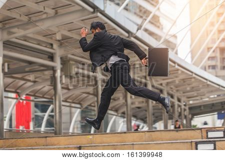 Businessman  Holding Bag And Running Rapidly To Airport In Formal Suit. In Rush Hour At Stairway In