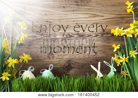 Wooden Background With English Quote Enjoy Every Moment. Easter Decoration Like Easter Eggs And Easter Bunny. Sunny Yellow Spring Flower Narcisssus With Gras. Card For Seasons Greetings