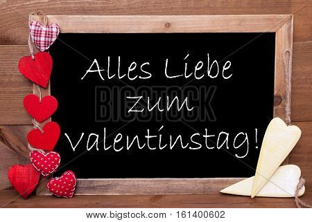 Chalkboard With German Text Alles Liebe Zum Valentinstag Means Happy Valentines Day. Red Textile And Wooden Yellow Hearts. Wooden Background With Vintage, Rustic Or Retro Style.