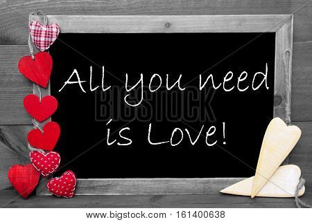 Chalkboard With English Quote All You Need Is Love. Red Hearts. Wooden Background With Vintage, Rustic Or Retro Style. Black And White Image With Colored Hot Spots.