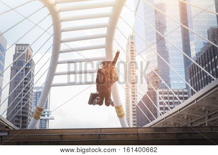 Business woman holding bag and jump over the stair in winner pose with formal suit. In rush hour at stairway in city. Business in the city concept.