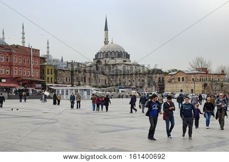 Istanbul Turkey - March 29 2013: Around the buildings the historic mosque and the people traveling with the Eminonu square