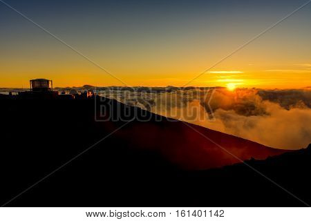 Sunset at the summit of Haleakala National Park with the observatory in the background Maui Hawaii USA