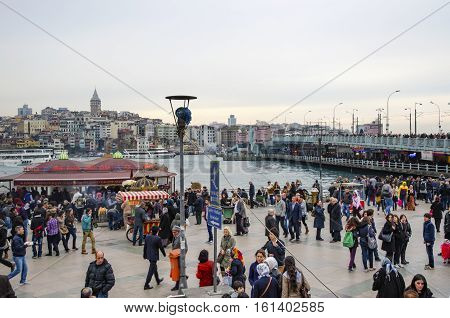 Istanbul Turkey - March 29 2013: Eating Grilled Fish Sandwich in Eminonu. Galata Tower and Galata Bridge on the rear are visible. The first thing that comes to mind when thinking of Istanbul is Eminonu-Karakoy and the places selling grilled fish sandwiche