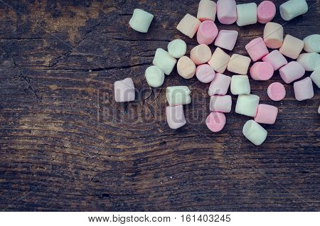Colorful marshmallows on an old rustic wooden table macro texture background with space for text. A pile of mini white pink and orange puffy marshmallows. Marshmallow concept. Copy space.