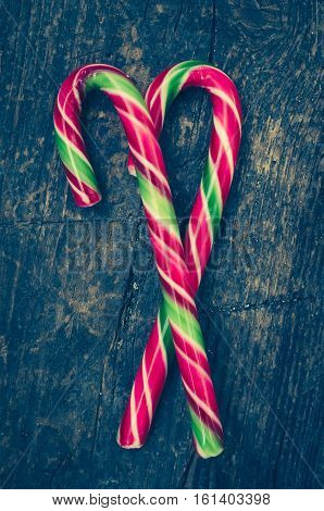 Striped Christmas candy canes on shabby chic wooden background. Red and green candy canes on weathered wooden board. Christmas Background. New Year Background.