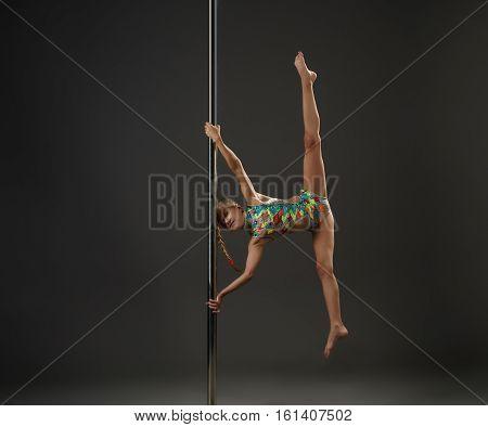 Teenaged girl in motley swimsuit making exercises on pilon in studio