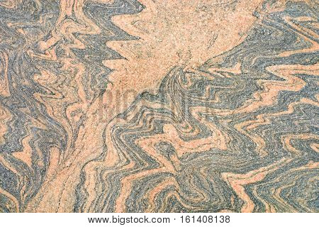 Patterned beige granite with blue veins. Natural stone texture