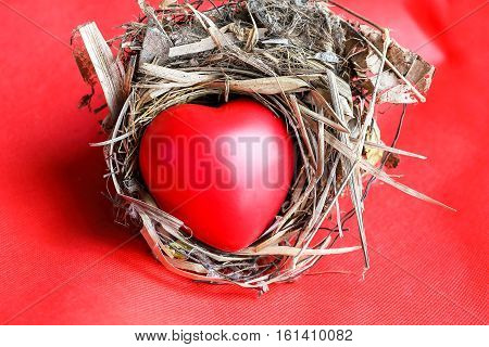 Red Love hart in bird nest straw leaf on red background