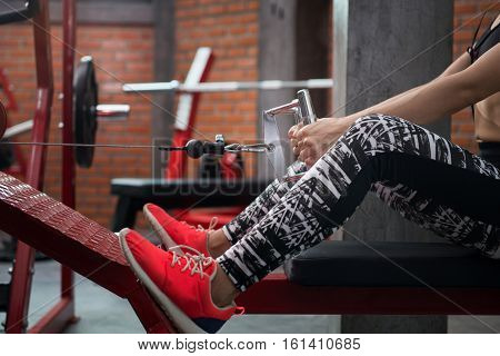 Close Up of young fitness woman executed exercise with exercise-machine Cable Crossover at fitness center.