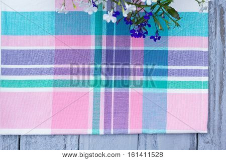 Close up on checkered tablecloth fabric. pink green violet with white tartan square pattern with blooming lobelia flowers