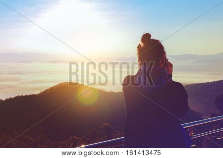 Silhouette of young woman taking photographer taking photo with mountain and more foggy in winter.