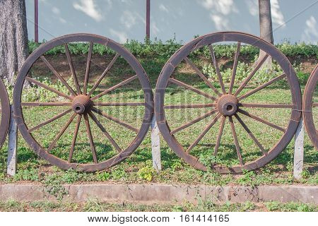 Old wooden cartwheel is fence for farm.