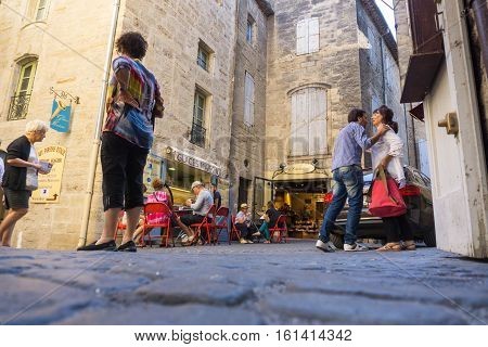 Pezanas, France - September 22, 2016: People greeting one and other, sitting at cafe's and walking through in Pezanas street scene from low point of view.