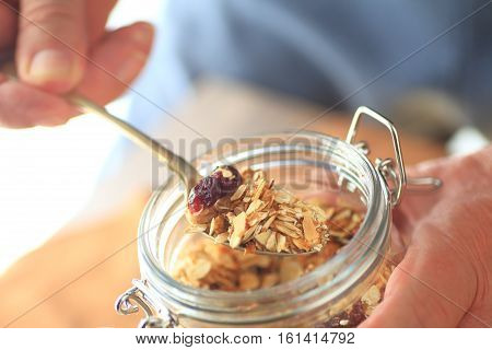 A man removes granola from a jar with a spoon