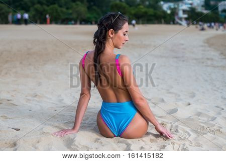 Back view of attractive sexy woman dressed in bikini sunbathing sitting on the beach enjoying summer holidays.