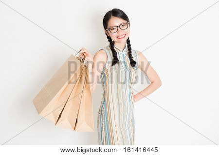 Portrait of young Asian girl in traditional qipao dress shopping, hand holding paper bag, celebrating Chinese Lunar New Year or spring festival, standing on plain background.