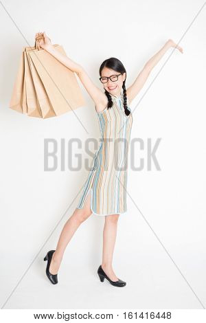 Portrait of young Asian woman in traditional qipao dress shopping, hand holding paper bag, celebrating Chinese Lunar New Year or spring festival, full body standing on plain background.