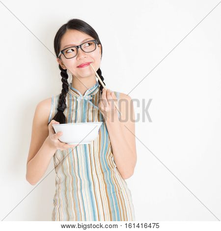 Portrait of young Asian woman in traditional qipao dress eating with chopsticks, celebrating Chinese Lunar New Year or spring festival, standing on plain background.