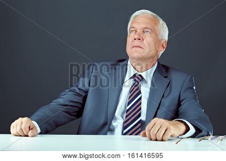 Portrait of senior businessman sitting at table and looking away