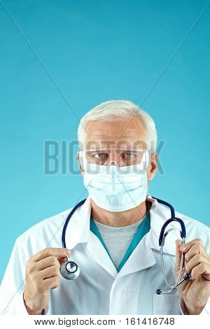 Portrait of mature medical doctor in mask and protective eyewear looking at camera