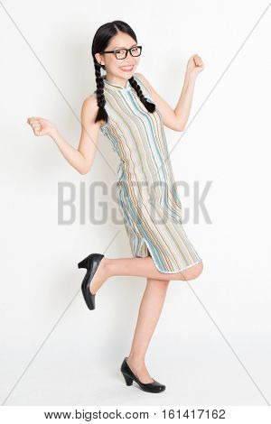 Portrait of excited young Asian girl in traditional qipao dress jumping around and hand holding something, full length standing on plain background.