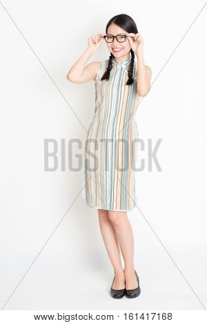 Portrait of young Asian girl in traditional qipao dress smiling, celebrating Chinese Lunar New Year or spring festival, full length standing on plain background.