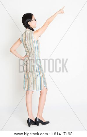 Rear view of young Asian girl in traditional qipao dress finger pointing away, full length standing on plain background.