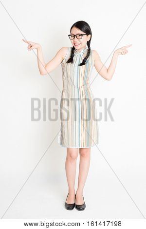 Portrait of young Asian woman in traditional qipao dress finger pointing at something, full length standing on plain background.