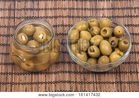 Green colossal olives hand stuffed with jalapeno peppers and garlic gloves in bowl on bamboo placemat