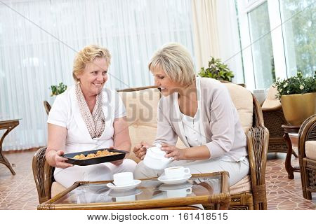 Senior woman treating her friend with cookies