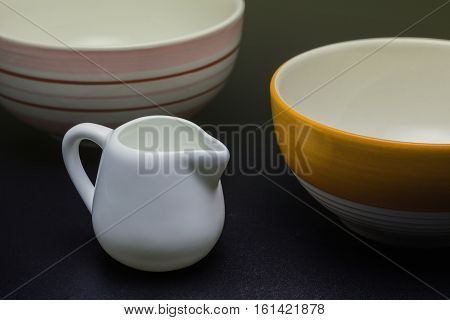 Small jug white jug with bowls on black background.