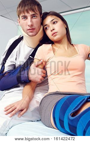 Sad young couple in hospital, men with broken arm and woman with broken leg