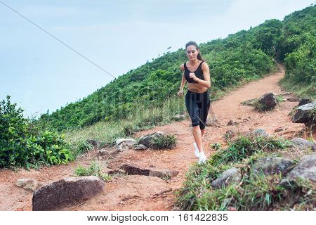 Sporty young woman in black sportswear trail running on mountain nature path. Fit girl jogging downhill on rocky track