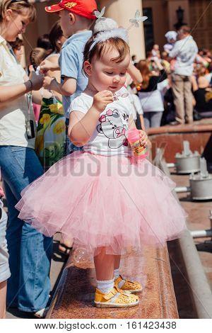 NOVOKUZNETSK KEMEROVO REGION RUSSIA - JUNE 01 2012 :: Children's protection day. Soup bubbles day selebration. Cute Little girl is blowing soap bubbles
