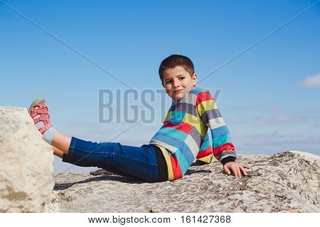 boy sitting on a rock holding up his feet on the stone
