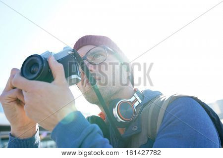 Hipster man taking pictures by the sea