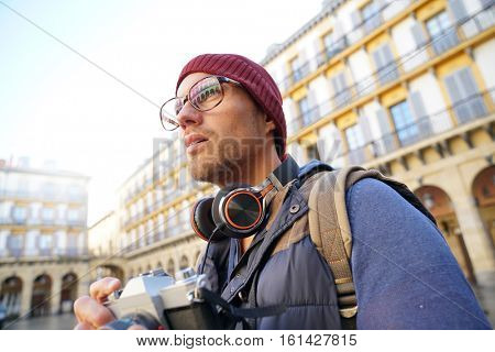 Hipster guy taking pictures in european city