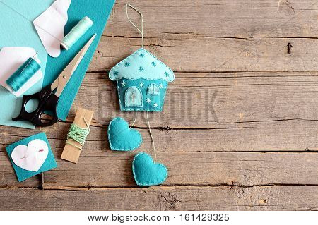Handmade felt house with hearts ornament, tools and materials for hand making felt crafts, paper templates on wooden background with copy space for text. Hanging wall decor. Children sewing workplace