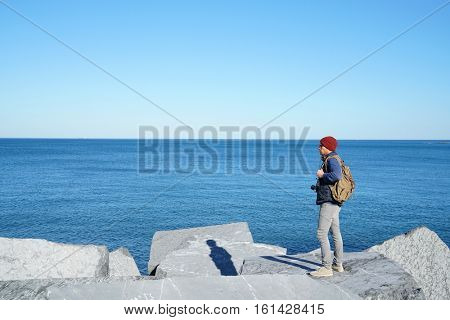 Man standing on rocks enjoying view of the ocean