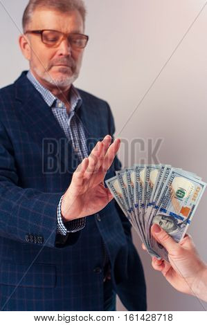 Portrait of senior businessman or manager rejecting bribe from partner. Bribery and corruption concept.