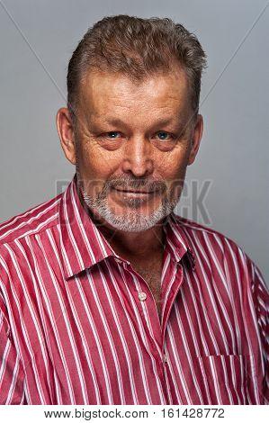 Portrait of confident attractive senior man on grey background.