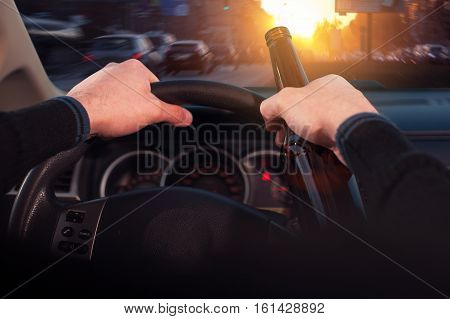 Cropped shot of male driver drinking beer while driving car.