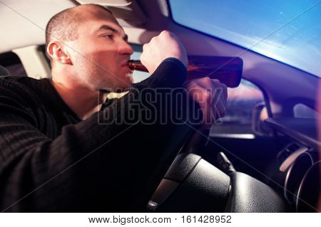 Young man drinking beer while driving a car. Drunk driver with bottle.