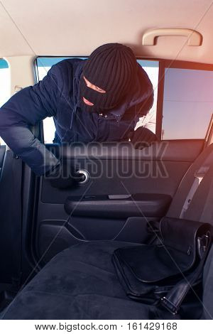 Thief in black robbery mask stealing handbag from the car