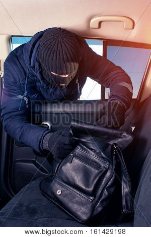 Robber in black mask stealing handbag from back seat.