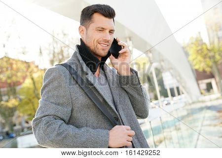 Handsome businessman talking on phone outside