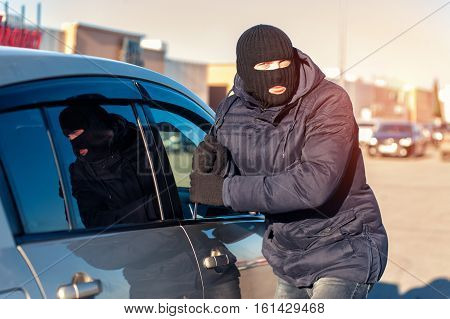 Thief in black robbery mask trying to break into car with screwdriver. Car theft.