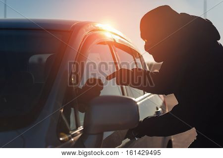 Car thief in black balaclava pointing to auto owner. Car theft.