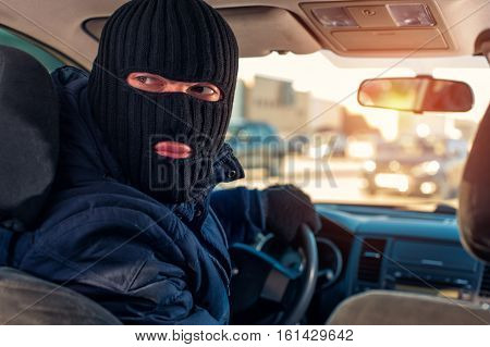 Male Robber In Black Mask Driving A Stolen Car